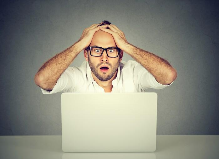 A man looks at a computer screen while clutching his head in apparent surprise.