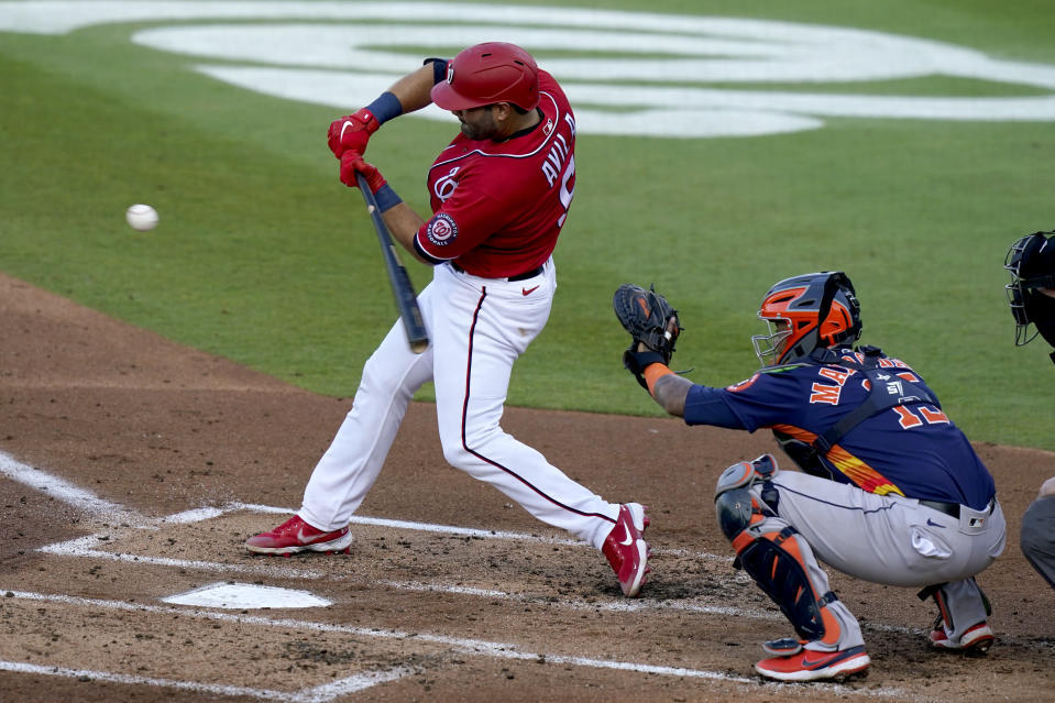 Washington Nationals' Alex Avila (6) hits a RBI single to score Kyle Schwarber during the first inning of a spring training baseball game against the Houston Astros, Wednesday, March 24, 2021, in West Palm Beach, Fla. At right is Houston Astros catcher Martin Maldonado. (AP Photo/Lynne Sladky)