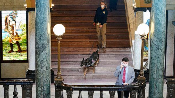 PHOTO: Deputy State Fire Marshal Kayla Riggs follows the agency's explosive detection dog, 'Ringo,' down the steps of the third floor at the Capitol in Jackson, Miss., Jan. 14, 2021. (Rogelio V. Solis/AP)