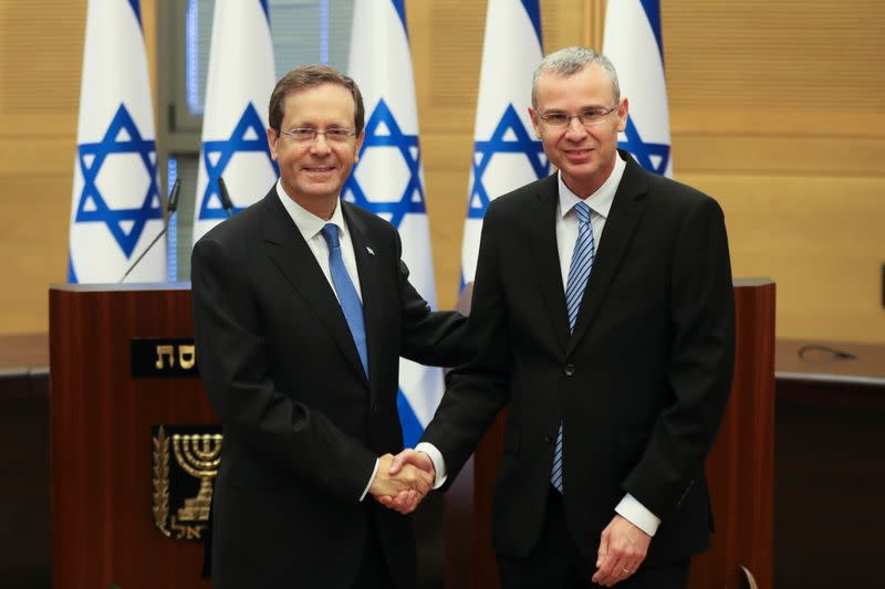 Presidential candidate Isaac Herzog shakes hands with Yariv Levin, Speaker of the Knesset, during a special session of the Knesset whereby Israeli lawmakers elect a new president, at the plenum in the Knesset, Israel's parliament, in Jerusalem