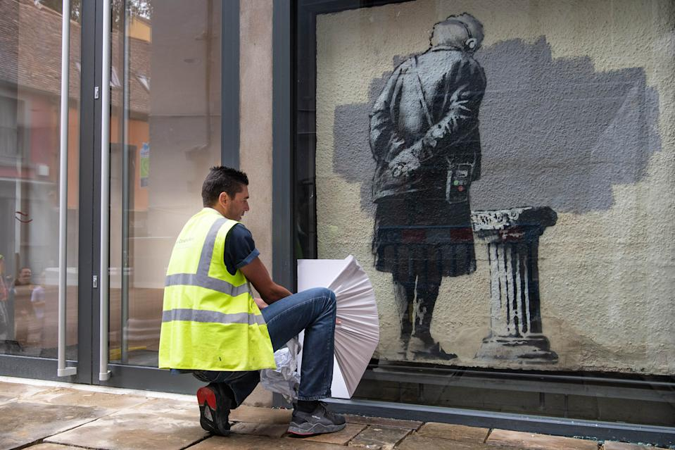EDITORIAL USE ONLY Art Buff, a painting by street artist Banksy, is re-installed on Folkestone's Old High Street, as Creative Folkestone announces a new art project called The Plinth � placing 10 vacant plinths in various locations around the seaside town and inviting residents and visitors to use them to display their artistic talents.