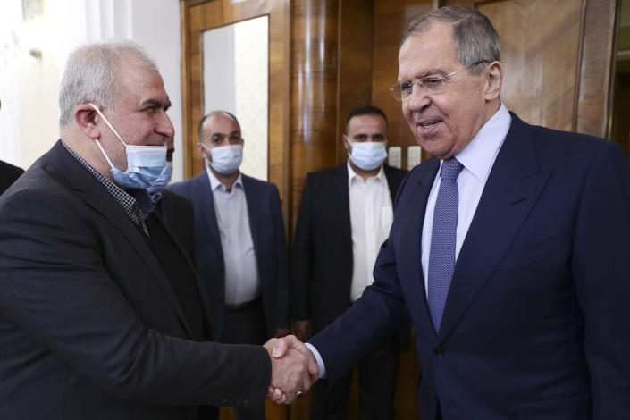 In this photo released by Russian Foreign Ministry Press Service, Russian Foreign Minister Sergey Lavrov, right, shakes hands with the head of Hezbollah parliamentary bloc Mohamad Raad during their meeting in Moscow, Russia, Monday, March 15, 2021. (Russian Foreign Ministry Press Service via AP)