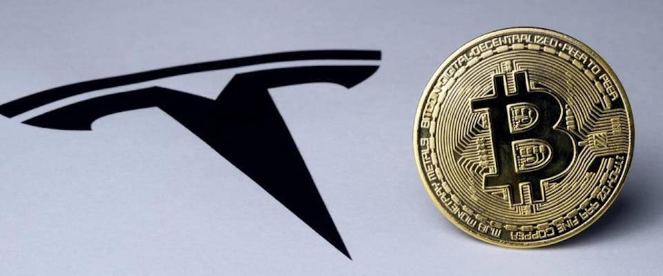 Bitcoin and Tesla logo seen on paper document.