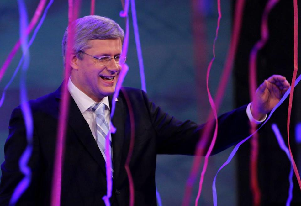Stephen Harper smiles and waves amid pink and purple streamers.