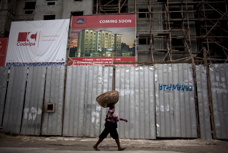 In this Thursday, April 26, 2012 photo, a street vendor walks in front of the building in construction of Best Western Hotel in Port-au-Prince, Haiti.  This city is undergoing the largest hotel building boom in its history, raising expectations that investors will soon fill those air-conditioned rooms looking to build factories, tourist infrastructure and other amenities that will help Haiti bounce back from the 2010 earthquake that killed hundreds of thousands of people. (AP Photo/Ramon Espinosa)