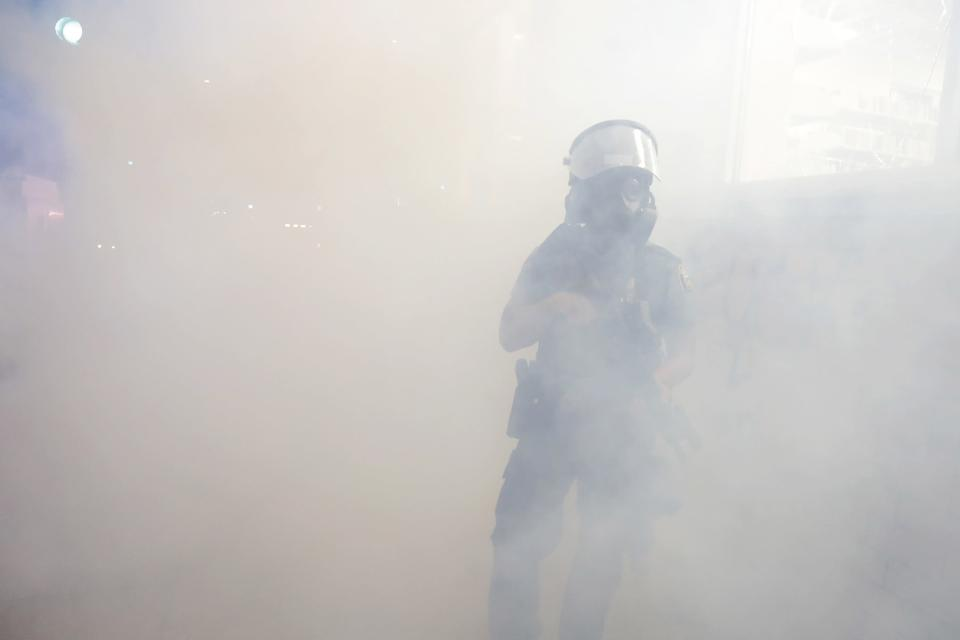 """FILE - In this May 28, 2020, file photo, a St. Paul Police officer walks among smoke after officers set off teargas on protesters in St. Paul, Minn. Former Minneapolis police Officer Derek Chauvin faces decades in prison when he is sentenced Friday, June 25, 2021, following his murder and manslaughter convictions in the death of George Floyd. Floyd's death, filmed by a teenage bystander as Chauvin pinned Floyd to the pavement for about 9 and a half minutes and ignored Floyd's """"I can't breathe"""" cries until he eventually grew still, reignited a movement against racial injustice that swiftly spread around the world and continues to reverberate. (AP Photo/Julio Cortez, File)"""