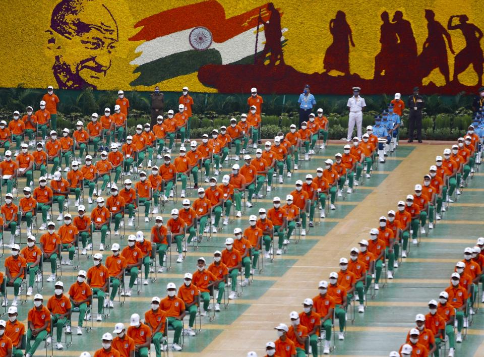 People dressed in the colors of the Indian national flag listens to Prime Minister Narendra Modi speaking from the ramparts of the historic Red Fort monument on Independence Day in New Delhi, India, Saturday, Aug. 15, 2020. (AP Photo/Manish Swarup)