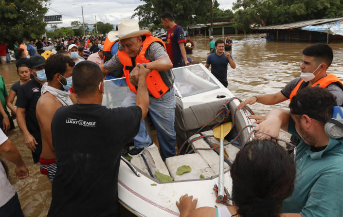 A resident is helped off a boat after he was rescued from a flooded area in the neighborhood of Planeta, Honduras, Thursday, Nov. 5, 2020. The storm that hit Nicaragua as a Category 4 hurricane on Tuesday had become more of a vast tropical rainstorm, but it was advancing so slowly and dumping so much rain that much of Central America remained on high alert. (AP Photo/Delmer Martinez)