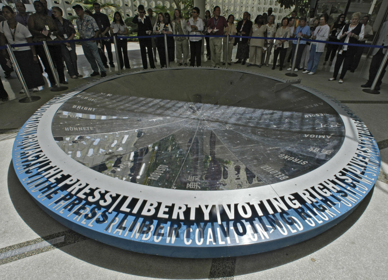 Los Angeles International Airport workers, travelers and community representatives hold a moment of silence in remembrance the third anniversary of Sept. 11, 2001 terrorist attacks, Thursday, Sept. 9, 2004, around the permanent art piece titled ``Recovering Equilibrium'' located at the Landmark Theme Building in the Central Terminal Area of the airport in Los Angeles. (AP Photo/Damian Dovarganes)