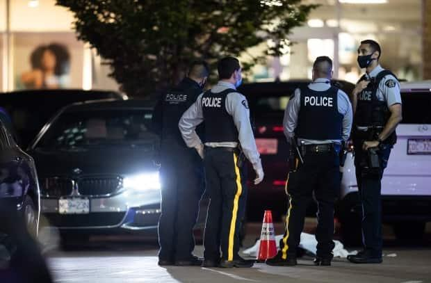 RCMP officers stand near a body covered with a tarp as bullet holes are seen in the windshield of a vehicle in the parking lot of the Market Crossing shopping complex in Burnaby, B.C., Thursday night. (Darryl Dyck/The Canadian Press - image credit)