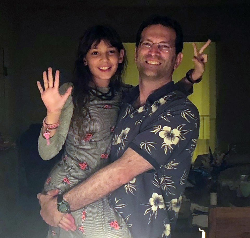 """In this circa 2016/2017 photo provided by Soriya Cohen, Dr. Brad Cohen poses with his daughter Elisheva in their Miami home. Brad Cohen is one of the people identified on Friday, July 16, 2021, as having died in the collapse of the Champlain Towers South condominium complex, in Surfside, Fla. The shirt worn in the picture by Brad Cohen is his wife, Soriya's favorite. His mother bought it for him early in Brad and Soriya's marriage. """"If I could have only one piece of clothing from him, it would be that shirt,"""" said Soriya. (Soriya Cohen via AP)"""