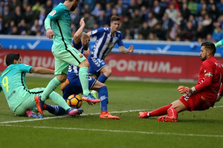 Barcelona's Luis Suarez (L) and Lionel Messi compete for the ball with Deportivo Alaves goalkeeper Fernando Pacheco (R) during their Spanish La Liga match, at the Mendizorroza stadium in Vitoria, in Feburary 2017