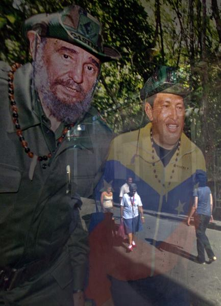 Pedestrians are reflected in a framed image of Cuba's Fidel Castro, left, and Venezuela's President Hugo Chavez, hanging inside a shop in Havana, Cuba, Friday, Jan. 4, 2013. Chavez hasn't spoken publicly or been seen since his Dec. 11 operation in Cuba, and the latest report from his government Thursday night increased speculation that he is unlikely to attend his Jan. 10 inaugural ceremony. (AP Photo/Ramon Espinosa)