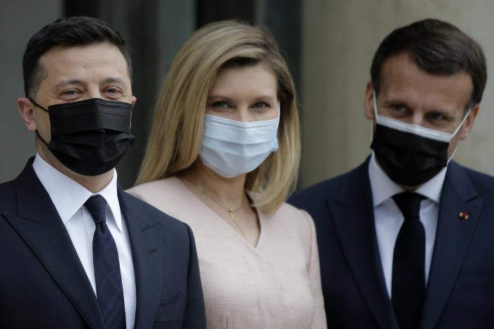 French President Emmanuel Macron, right, poses with Ukrainian President Volodymyr Zelenskyy, left, and Olena Zelenska before a working lunch at the Elysee palace in Paris, Friday, April 16, 2021. Ukrainian President Volodymyr Zelenskyy is holding talks with French President Emmanuel Macron and German Chancellor Angela Merkel amid growing tensions with Russia, which has deployed troops at the border with the country. (AP Photo/Lewis Joly)