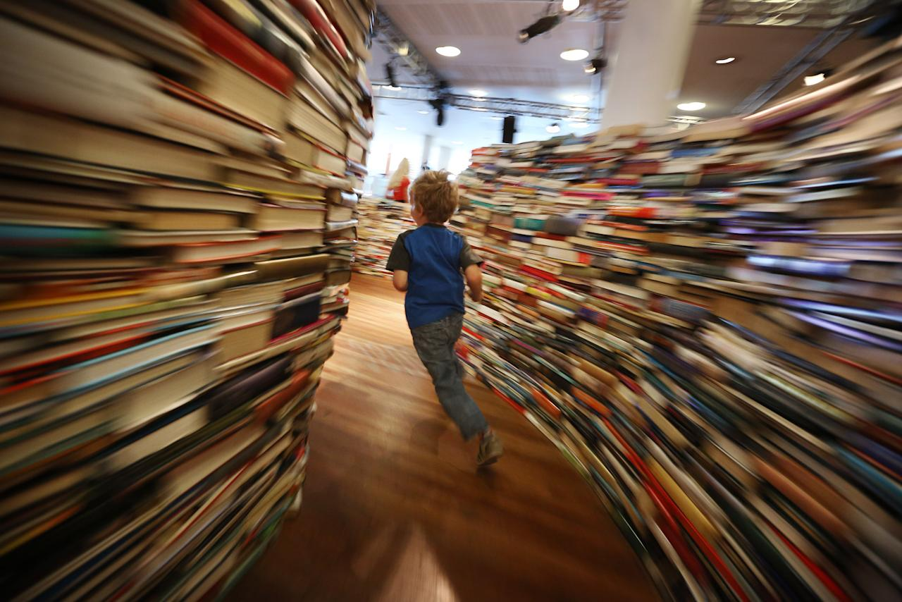 A child runs in the 'aMAZEme' labyrinth made from books at The Southbank Centre on July 31, 2012 in London, England. (Photo by Peter Macdiarmid/Getty Images)