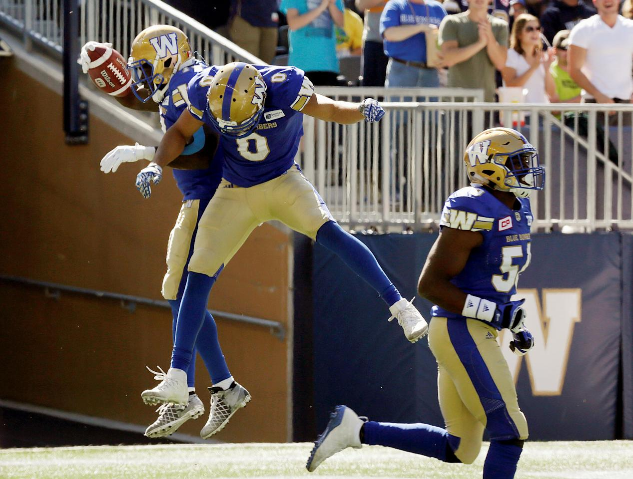 CFL Football - Winnipeg Blue Bombers v Toronto Argonauts - Winnipeg, Manitoba, Canada - 17/9/16 - Winnipeg Blue Bombers Quincy McDuffie celebrates his 98 yard kickoff return for a touchdown with teammates Derek Jones and Kyle Knox.   REUTERS/Lyle Stafford