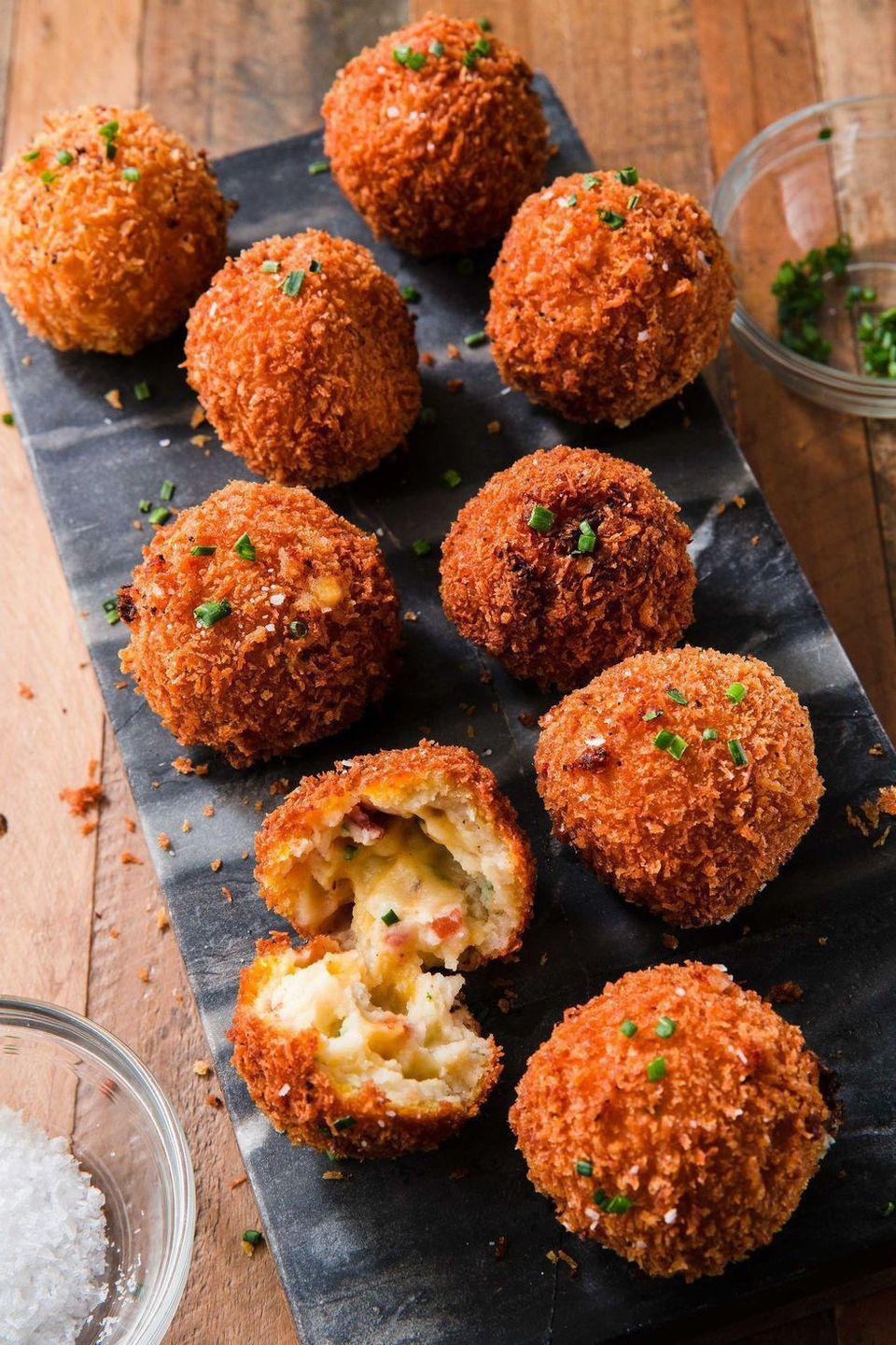 """<p>Even more decadent than the potatoes served on Thanksgiving, these fried beauties are taken to the next level with bacon and cheddar cheese. </p><p><em><a href=""""https://www.delish.com/cooking/recipe-ideas/a22566735/fried-mashed-potato-balls-recipe/"""" rel=""""nofollow noopener"""" target=""""_blank"""" data-ylk=""""slk:Get the recipe from Delish »"""" class=""""link rapid-noclick-resp"""">Get the recipe from Delish »</a></em></p>"""