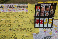 A man holds a poster featuring famous pro-democracy activists outside a court in Hong Kong Monday, March 1, 2021. People gathered outside the court Monday to show support for 47 activists who were detained over the weekend under a new national security law that was imposed on the city by Beijing last year. (AP Photo/Vincent Yu)