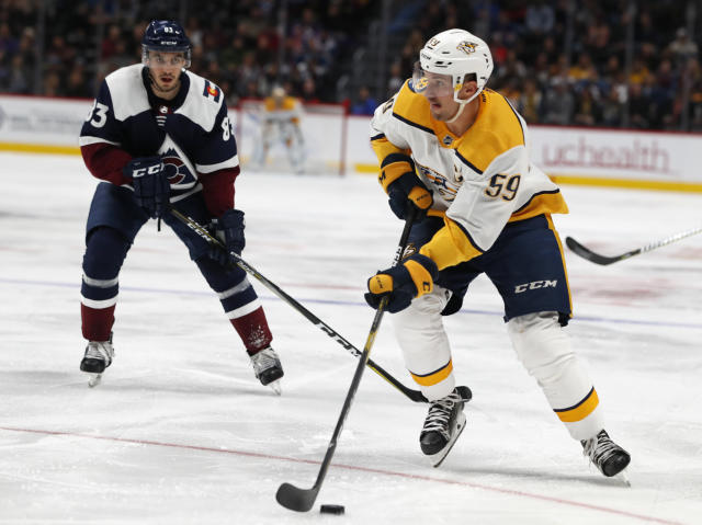Nashville Predators defenseman Roman Josi, front, drives to the net past Colorado Avalanche left wing Matt Nieto during the second period of an NHL hockey game Wednesday, Nov. 7, 2018, in Denver. (AP Photo/David Zalubowski)