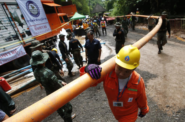 <p>Rescuers carrying a water pipe make their way to the entrance to a cave complex where 12 boys and their soccer coach were trapped inside when heavy rains flooded the cave, in Mae Sai, Chiang Rai Province, northern Thailand, July 4, 2018. (Photo: Sakchai Lalit/AP) </p>