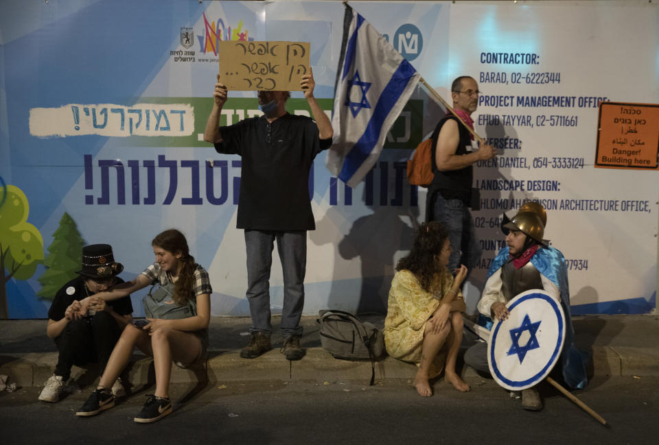 Israeli protesters hold signs during a demonstration against Israeli Prime Minister Benjamin Netanyahu outside his official residence in Jerusalem, Saturday, June 12, 2021. If all goes according to plan, Israel will swear in a new government on Sunday, ending Prime Minister Benjamin Netanyahu's record 12-year rule and a political crisis that inflicted four elections on the country in less than two years. (AP Photo/Ariel Schalit)