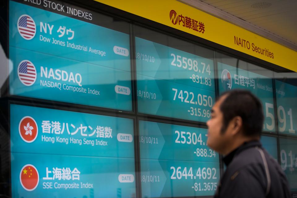 On the up? A pedestrian looks at a stock indicator board showing Dow Jones, NASDAQ, Hang Seng and SSE composite index numbers, in Tokyo on October 11, 2018. Photo: BEHROUZ MEHRI/AFP/Getty Images.