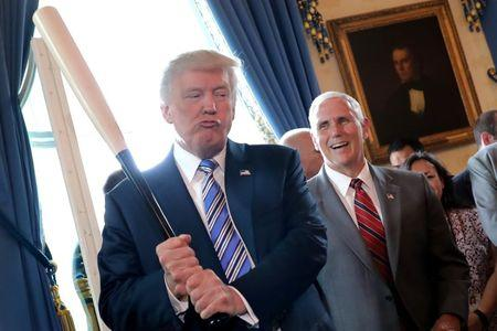 Vice President Mike Pence laughs as U.S. President Donald Trump holds a baseball bat as they attend a Made in America product showcase event at the White House in Washington, U.S.