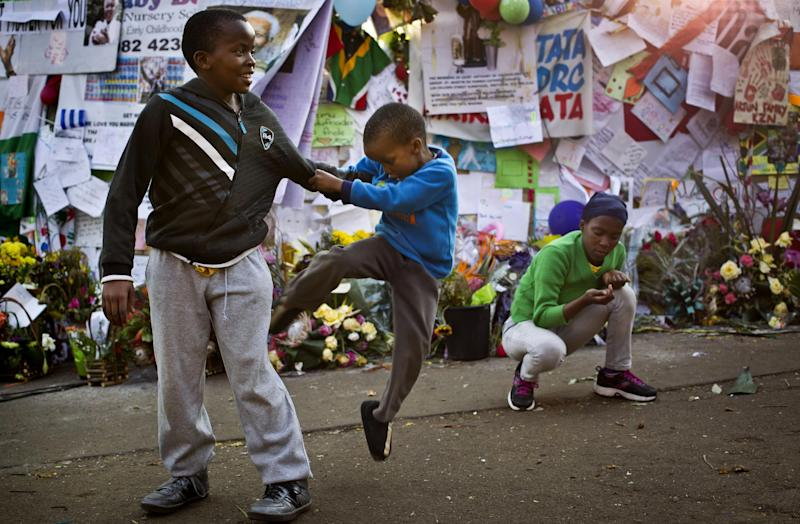 Boys play-fight next to a wall of get-well messages and flowers laid outside the Mediclinic Heart Hospital where former South African President Nelson Mandela is being treated in Pretoria, South Africa Monday, July 8, 2013. There was no official update Monday morning on the health of the 94-year-old former president and anti-apartheid leader, who was admitted June 8 to the hospital for a recurring lung infection. (AP Photo/Ben Curtis)