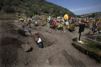 "A cemetery worker digs a grave at the municipal cemetery Valle de Chalco amid the new coronavirus pandemic, on the outskirts of Mexico City, Tuesday, Oct. 20, 2020. Mexican families traditionally flock to local cemeteries to honor their dead relatives as part of the ""Dia de los Muertos,"" or Day of the Dead celebrations, but according to authorities the cemeteries will be closed this year to help curb the spread of COVID-19. (AP Photo/Marco Ugarte)"