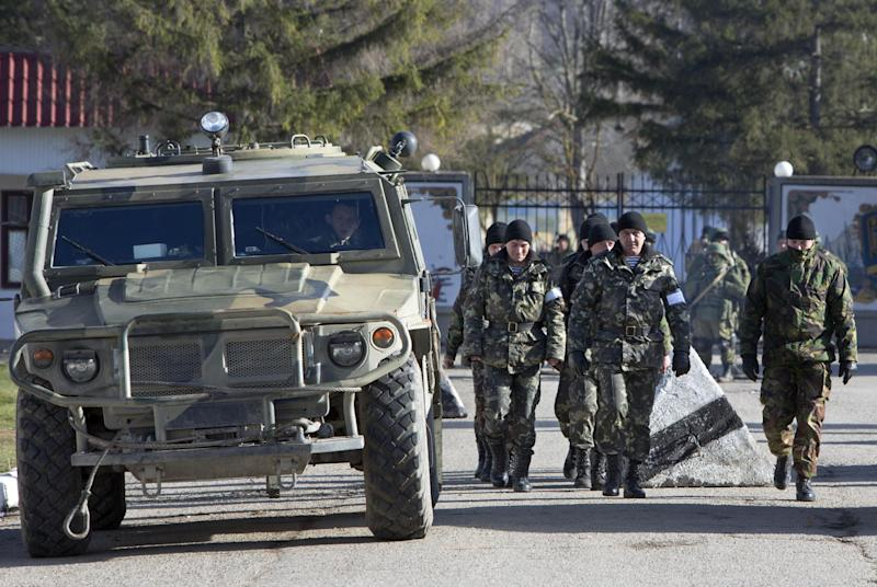 Ukrainian troops with white bands on their sleeves march past an unmarked Russian military vehicle outside a Ukrainian military base in Perevalne, Crimea, Ukraine, Monday, March 17, 2014. Crimea held a referendum Sunday, in which an overwhelming majority voted for breaking off from Ukraine and joining Russia. (AP Photo/Andrei Udovichenko)
