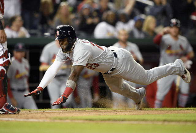St. Louis Cardinals' Marcell Ozuna, right, starts his slide toward home to score on a double by Jose Martinez during the fifth inning of a baseball game against the Washington Nationals, Monday, April 29, 2019, in Washington. (AP Photo/Nick Wass)