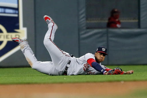 Washington Nationals left fielder Juan Soto hits the ground after diving to catch a shallow fly ball off the bat of Minnesota Twins' Willians Astudillo during the sixth inning of a baseball game Wednesday, Sept. 11, 2019, in Minneapolis. (AP Photo/Jim Mone)