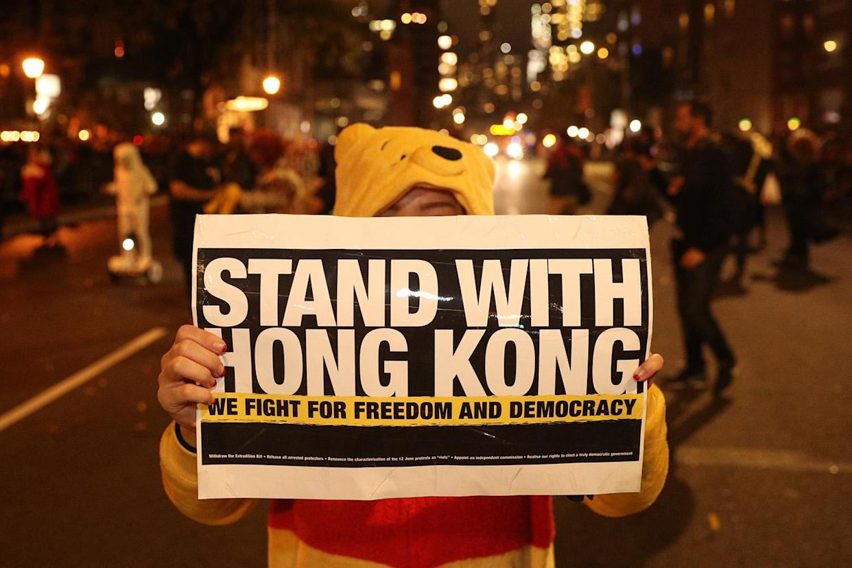 A reveler in costume holds up a political sign in support of Hong Kong during the 46th annual Village Halloween Parade in New York City. (Photo: Gordon Donovan/Yahoo News)