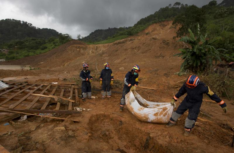 Soldiers remove the body of a woman who was recovered from the site of a landslide in La Pintada, Mexico, Saturday, Sept. 21, 2013. The village was the scene of the single greatest tragedy in destruction wreaked by the twin storms, Manuel and Ingrid, which simultaneously pounded both of Mexico's coasts. Using picks and shovels, soldiers and farmers removed dirt and rock from atop the cement or corrugated-metal roofs of houses looking for bodies in this town north of Acapulco, where 68 people were reported missing following Monday's slide. (AP Photo/Eduardo Verdugo)