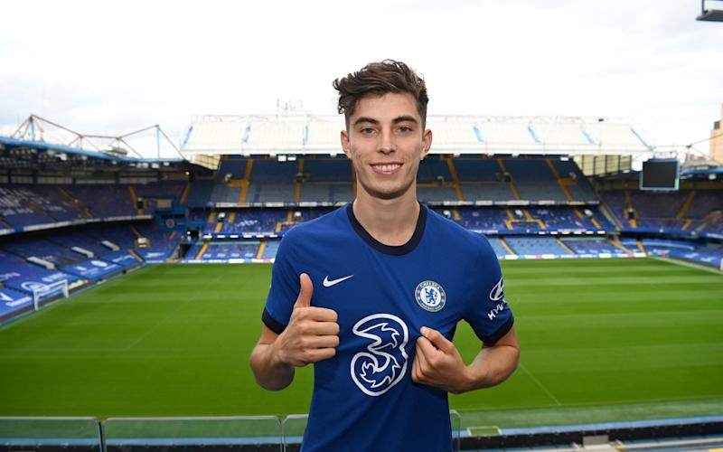 Kai Havertz wearing the Chelsea home shirt poses for the camera as Chelsea - Getty Images