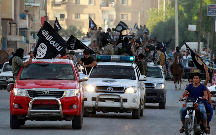 Islamic State fighters wave flags on a military parade in Raqqa province - Reuters