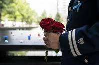 A mourner brings roses to the north pool after the conclusion of ceremonies to commemorate the 20th anniversary of the Sept. 11 terrorist attacks, Saturday, Sept. 11, 2021, at the National September 11 Memorial & Museum in New York. (AP Photo/John Minchillo)