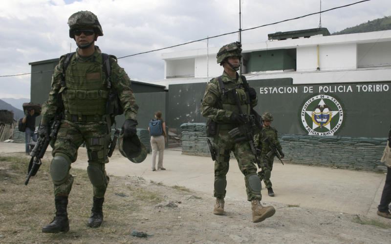 Soldiers patrol in front the police station that was attacked by rebels of the Revolutionary Armed Forces of Colombia (FARC) last week in Toribio, southern Colombia, Tuesday, July 10, 2012. Colombia's President Juan Manuel Santos will visit Toribio on Wednesday. (AP Photo/Juan Bautista)