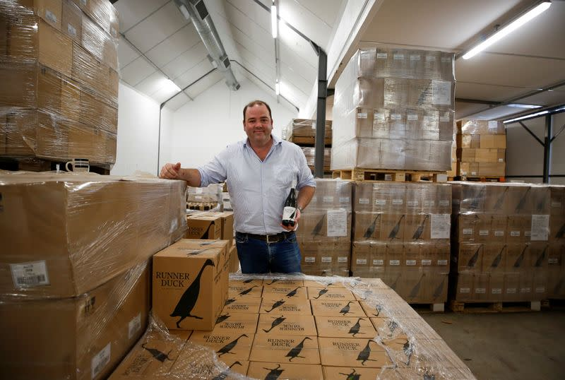 Shaun Mcvey of Vergenoegd Low Wine Estate stands amongst cases of Runner Duck wines, near Cape Town