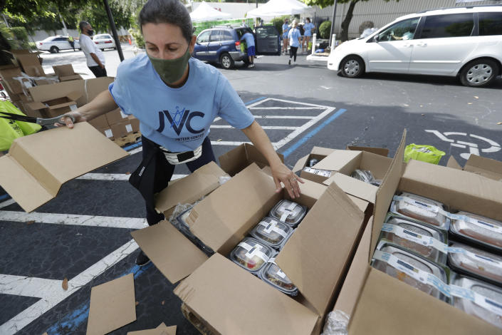 Volunteer Malka Rodrig unpacks meals at a kosher food drive-thru distribution site, Wednesday, July 29, 2020, at the Greater Miami Jewish Federation building in Miami. (AP Photo/Wilfredo Lee)