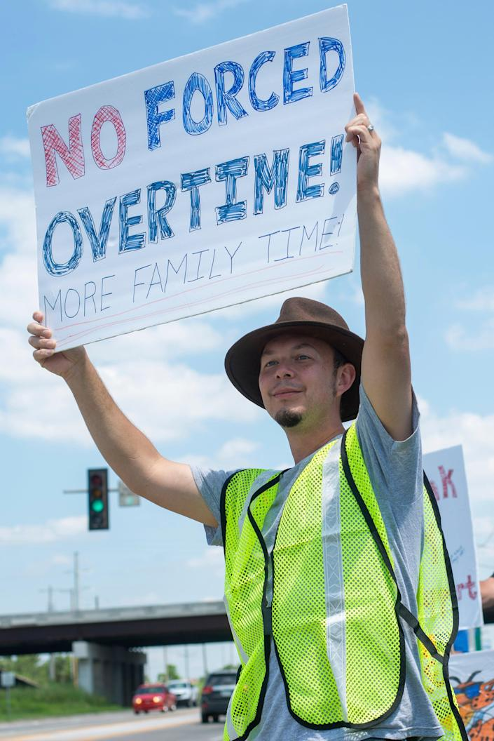 Monk Drapeaux-Stewart holds a sign reflecting compromising work-life balance during a strike against Frito-Lay outside of the plant in Topeka, Kansas Tuesday 13 July 13 2021. (AP)