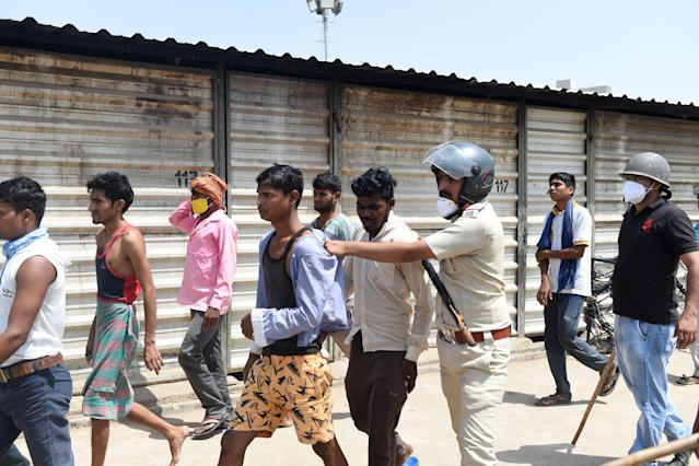 Gujarat police personnel detain migrant workers over a stone pelting incident in Ahmedabad. (Photo by SAM PANTHAKY/AFP via Getty Images)