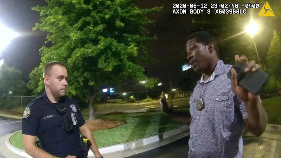 In this June 12, 2020, file photo from a screen grab taken from body camera video provided by the Atlanta Police Department Rayshard Brooks, right, speaks with Officer Garrett Rolfe, left, in the parking lot of a Wendy's restaurant, in Atlanta. Former Atlanta Police Officer, Rolfe's attorney said Thursday, April 22, 2021, that his client didn't get a chance to defend himself before he was fired for fatally shooting Brooks, a Black man who had been running away from two white officers after he resisted arrest and fired a stun gun at one of them. (Atlanta Police Department via AP, File)