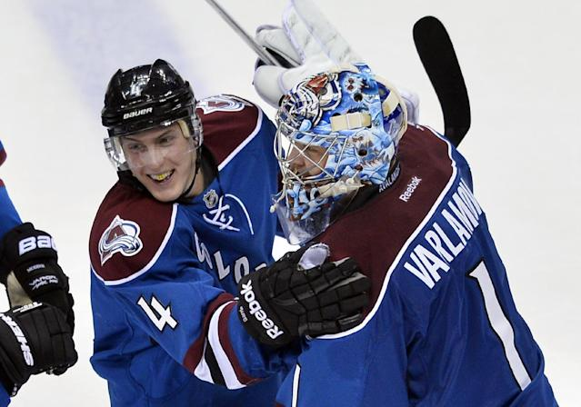 Colorado Avalanche defenseman Tyson Barrie (4) is congratulated by Semyon Varlamov (1) after scoring in overtime against the Vancouver Canucks during an NHL hockey game, Thursday, March 27, 2014, in Denver. Colorado won 3-2. (AP Photo/Jack Dempsey)