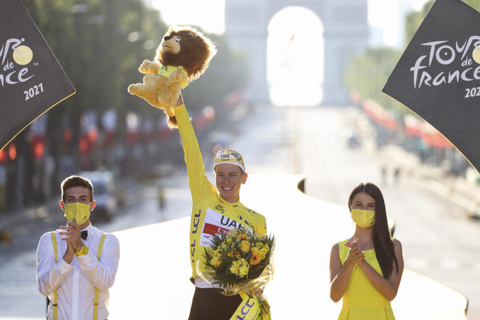 Tour de France winner Slovenia's Tadej Pogacar, wearing the overall leader's yellow jersey, celebrates on the podium after the twenty-first and last stage of the Tour de France cycling race over 108.4 kilometers (67.4 miles) with start in Chatou and finish on the Champs Elysees in Paris, France,Sunday, July 18, 2021. (Garnier Etienne/L'Equipe via AP, Pool)