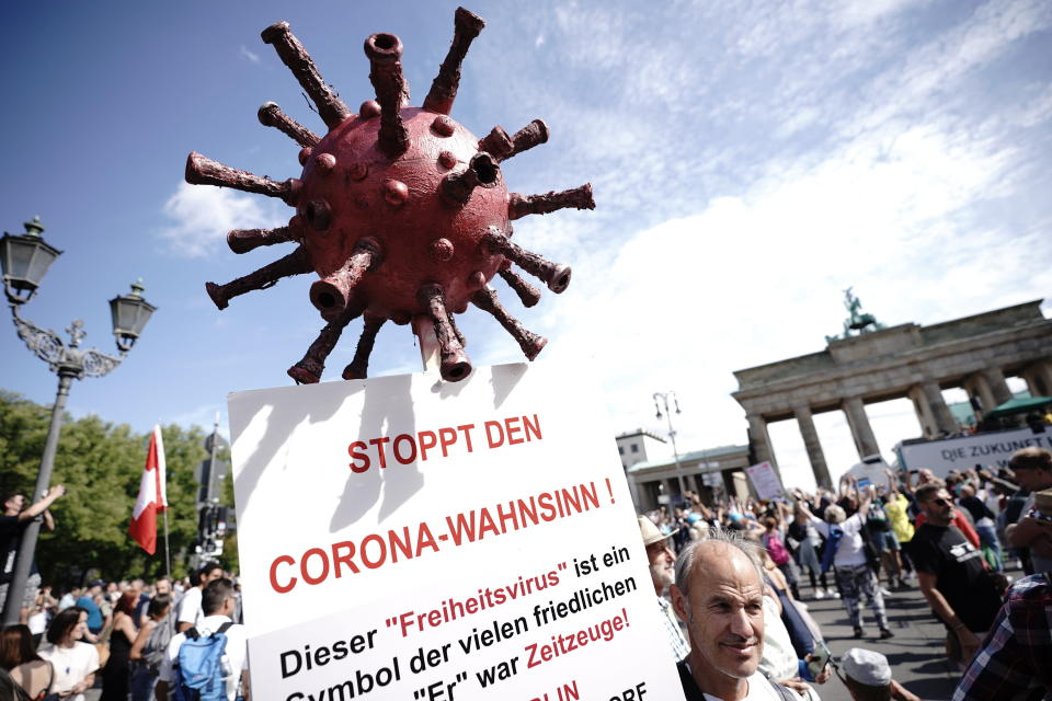 """A protestor holds a sign reading """"Stop the Corona Madness!"""" during demonstrations against the coronavirus measures by the German Government in Berlin, Germany, Saturday, Aug. 29, 2020. (Michael Kappeler/dpa via AP)"""