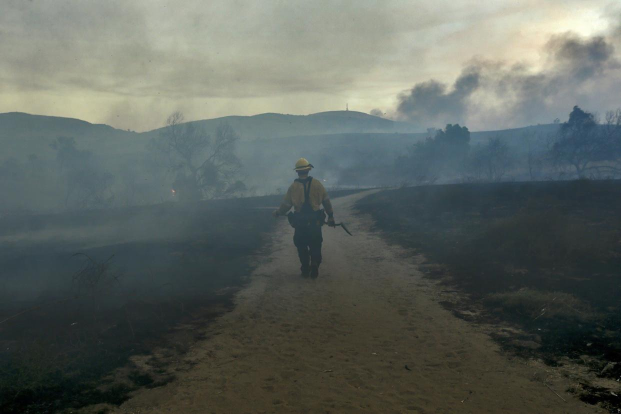 A fireman walks on trail looking for hotspots at Peters Canyon Regional Park in Orange, California.