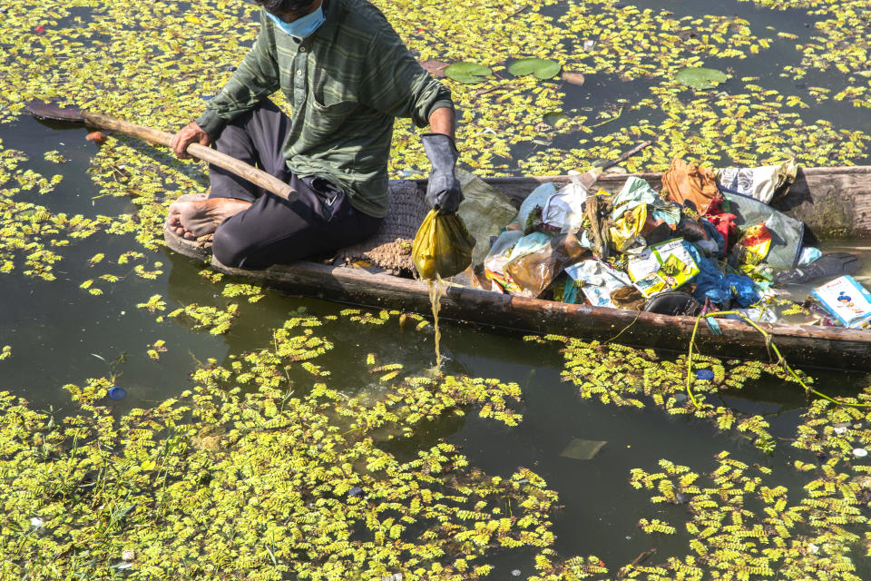 A Kashmiri boatman employed by the Lakes and Waterways Development Authority removes garbage from the Dal Lake in Srinagar, Indian controlled Kashmir, Tuesday, Sept. 14, 2021. Dal Lake appears pristine in the area where hundreds of exquisitely decorated houseboats bob on its surface for rent by tourists and honeymooners. But farther from shore, the lake is a mixture of mossy swamps, thick weeds, trash-strewn patches and floating gardens made from rafts of reeds. (AP Photo/Mukhtar Khan)