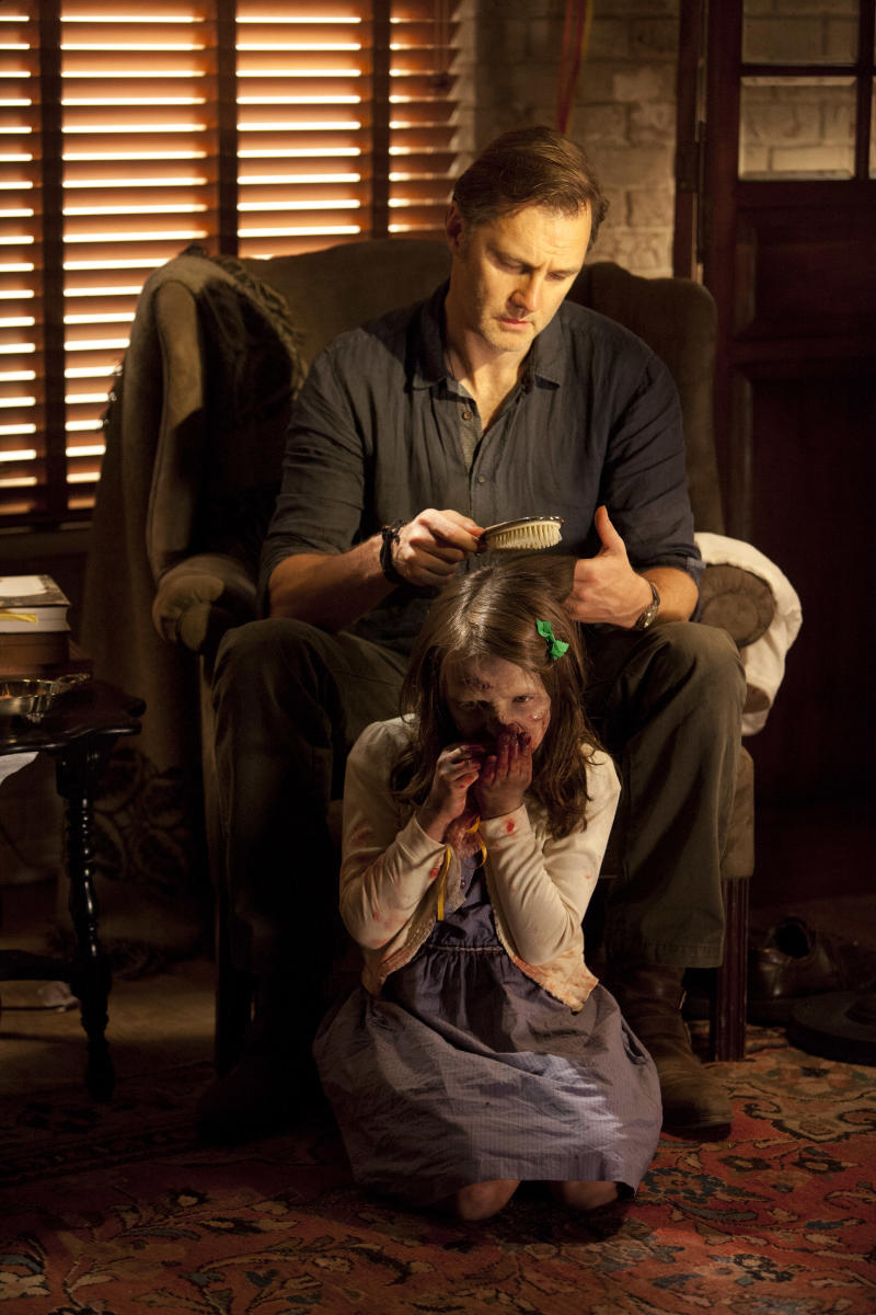 """This undated image released by AMC shows David Morrisey as The Governor brushing the hair of Kylie Szymanski as Penny in a scene from the third season of """"The Walking Dead."""" The popular zombie series returns for another eight episodes Sunday at 9 p.m. EST. (AP Photo/AMC, Russell Kaye)"""