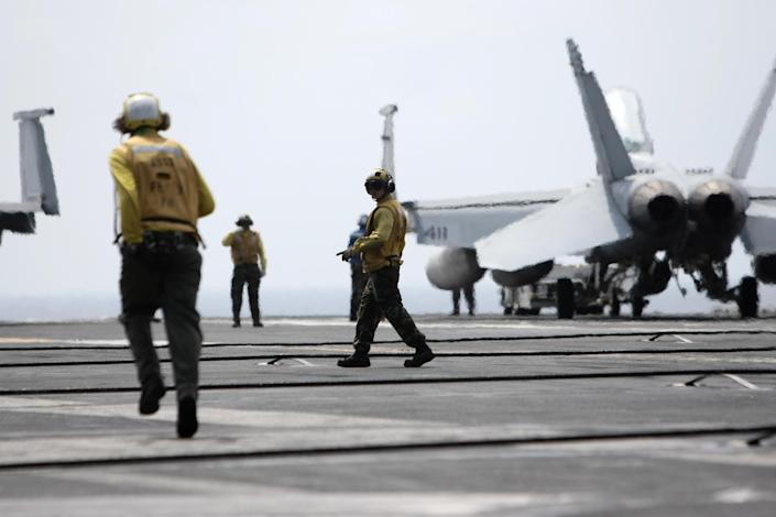 U.S. Navy technicians prepare for aircrafts to land on the deck of the nuclear-powered USS George Washington (CVN73) off southern coast of Vietnam in South China Sea Saturday, Oct. 20, 2012. A U.S. aircraft carrier group cruised through the disputed South China Sea on Saturday in a show of American power in waters that are fast becoming a focal point of Washington's strategic rivalry with Beijing. (AP Photo/Na Son Nguyen)